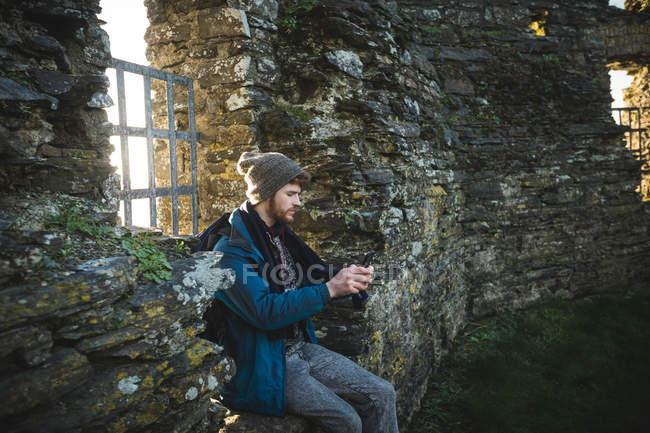 Мужчина турист с помощью мобильного телефона в старых руинах в сельской местности — стоковое фото
