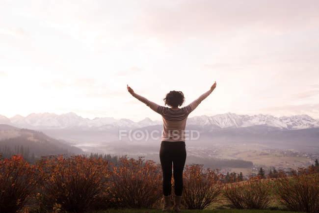 Vue arrière de la femme debout avec les bras tendus — Photo de stock