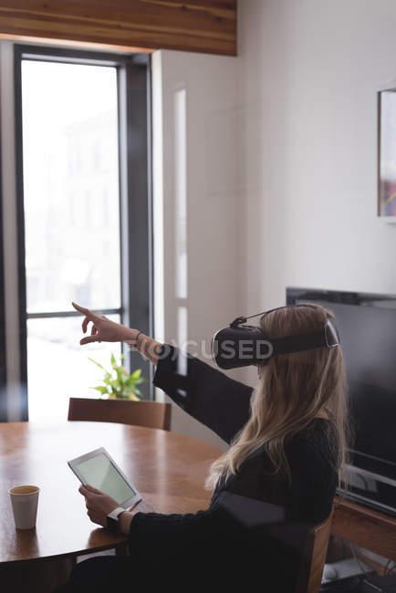 Executive femminile con auricolare realtà virtuale con tablet digitale in ufficio — Foto stock