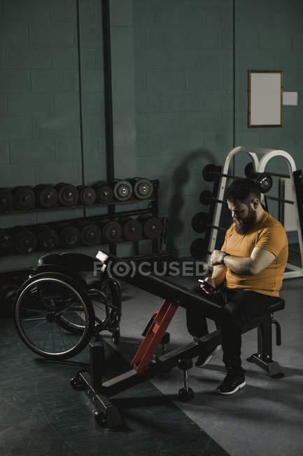 Недостатками человек, проверка мобильного телефона на жим в тренажерном зале — стоковое фото