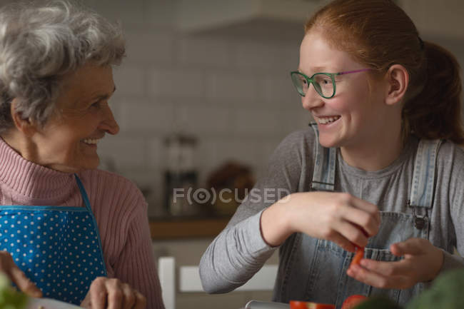 Grandmother and granddaughter smiling in kitchen at home — Stock Photo