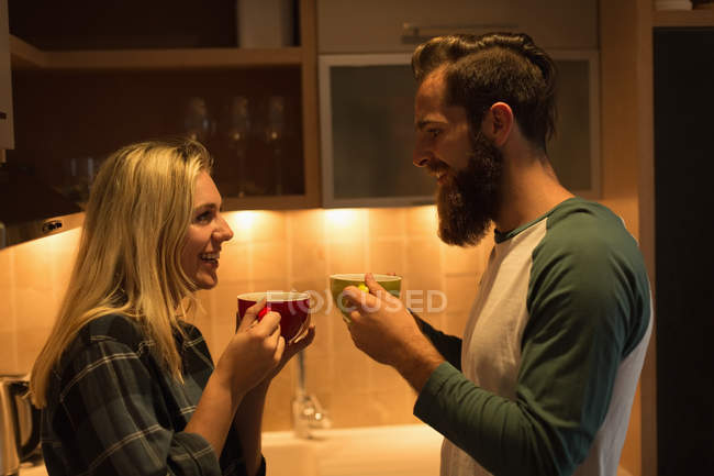 Pareja tomando café en la cocina en casa - foto de stock