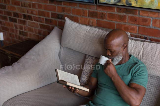 Seniorchef trinkt Kaffee, während er zu Hause ein Buch liest — Stockfoto