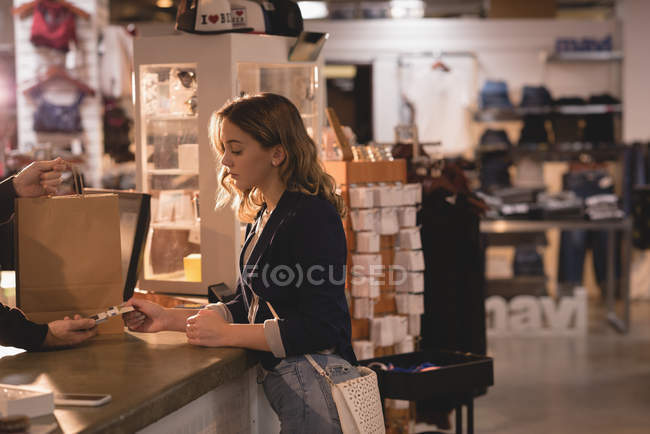 Girl making payment through card at counter — Stock Photo