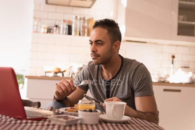 Homme prenant le petit déjeuner dans la cuisine à la maison . — Photo de stock