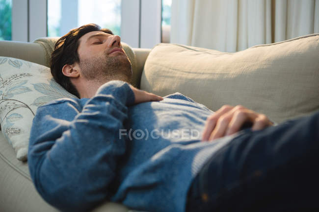 Man sleeping on sofa in living room at home — Stock Photo