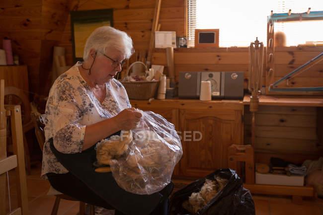 Sezione media di donna anziana che tiene il cotone in negozio — Foto stock