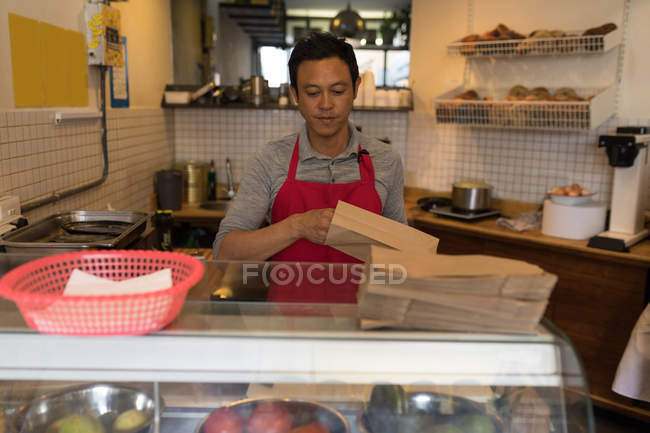 Male staff packing food in paper bag in coffee shop — Stock Photo