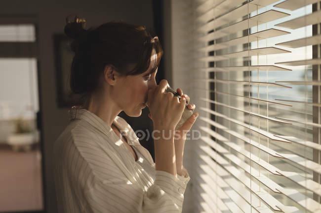 Jovem de pé perto da janela, tomando um café em casa — Fotografia de Stock