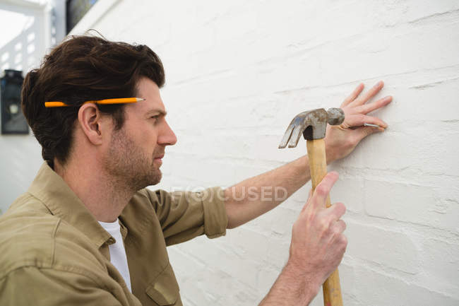 Young male carpenter hammering nail on wall — Stock Photo