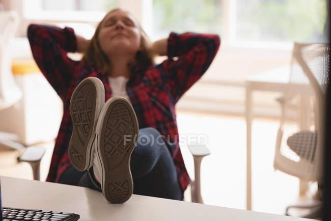 Exécutif féminin fatigué se détendre avec les pieds sur la table dans le bureau — Photo de stock