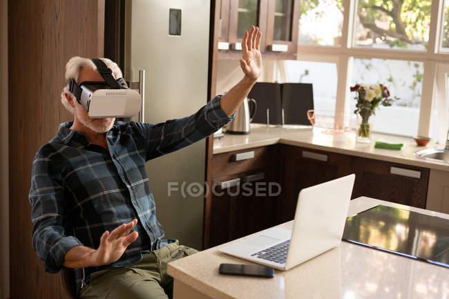 Старший мужчина использует гарнитуру виртуальной реальности с ноутбуком на кухне дома — стоковое фото