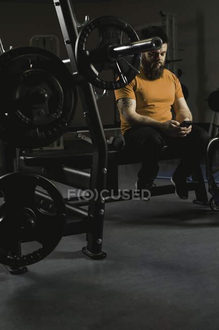 Недостатками человек, с помощью мобильного телефона на жим в тренажерном зале — стоковое фото