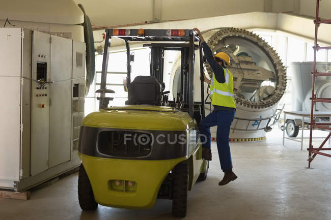 Male worker getting in forklift at solar station — Stock Photo