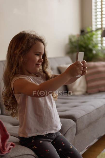 Fille mignonne prenant selfie avec téléphone portable dans le salon à la maison — Photo de stock