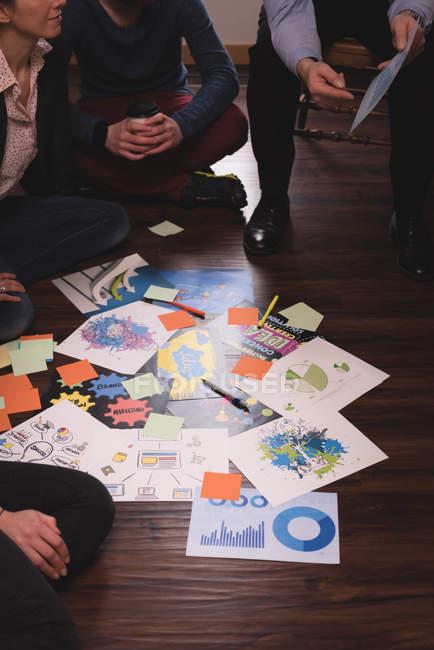 Коллеги по бизнесу обсуждают графические документы в офисе — стоковое фото