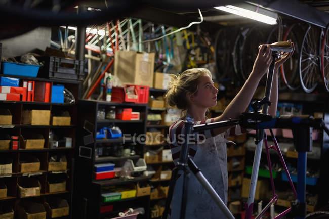 Молода жінка механік фіксації велосипеді в майстерні — стокове фото