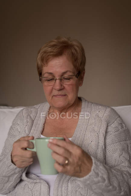 Senior woman having coffee in living room at home — Stock Photo