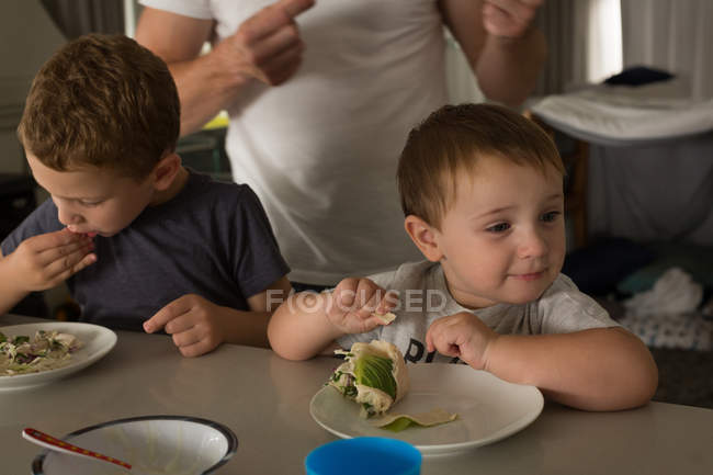 Батько і син, маючи сніданок посередині столу на дому — стокове фото