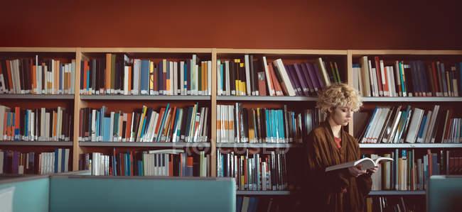 Молода жінка читає книжку в бібліотеці. — стокове фото