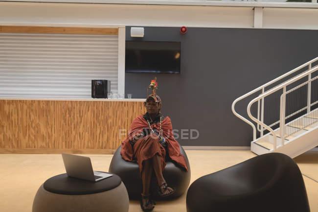 Масаї людина в традиційному одязі відпочиваючи на сидіння в торговий центр — стокове фото