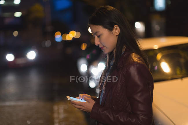 Woman using mobile phone in city street at night — Stock Photo