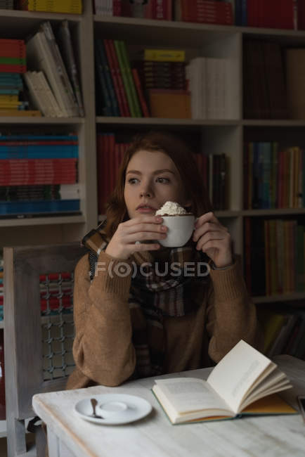 Thoughtful woman having dessert in library room — Stock Photo