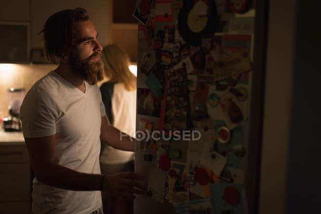 Mann, die Kühlschranktür zu öffnen, in der Küche zu Hause — Stockfoto