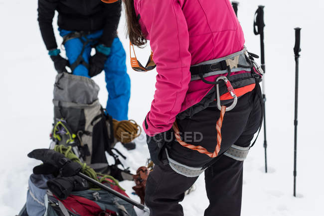 Couple wearing harness on a snow covered mountain during winter — Stock Photo
