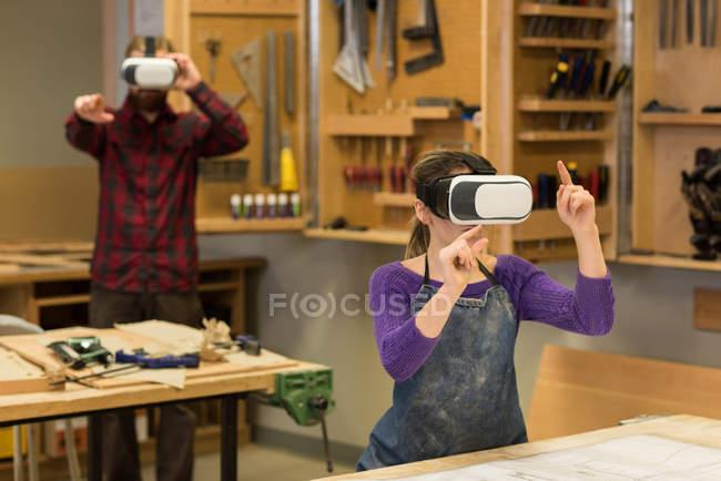 Carpinteros masculinos y femeninos usando auriculares de realidad virtual en el taller - foto de stock