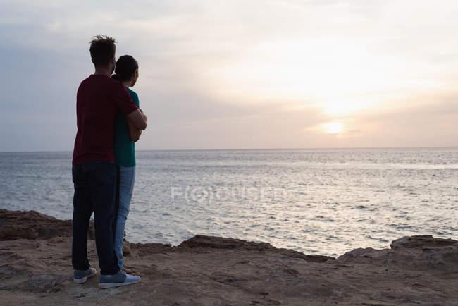 Romántica pareja abrazándose en la playa al atardecer - foto de stock