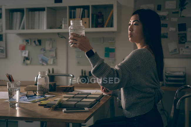 Female executive looking at jar in office — Stock Photo