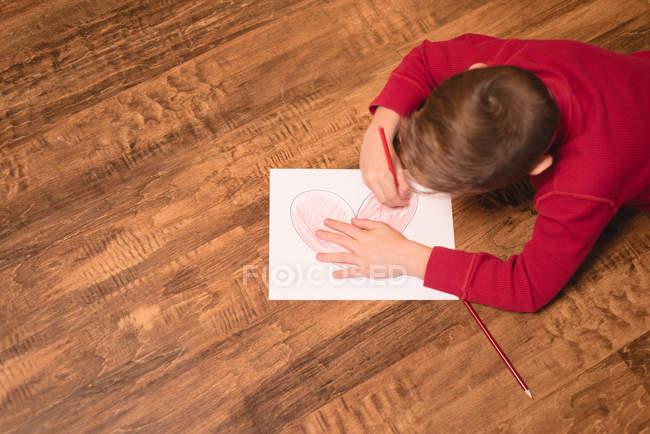 Menino desenho em papel artesanal em casa — Fotografia de Stock