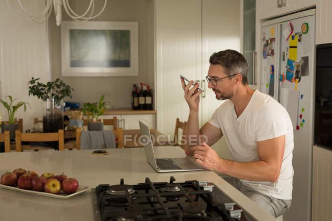 Людина, використовуючи ноутбук під час розмови по мобільному телефоні вдома — стокове фото