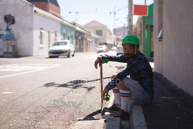 Вид збоку Скейтбордист розслабляючий на тротуарі на вулиці — стокове фото