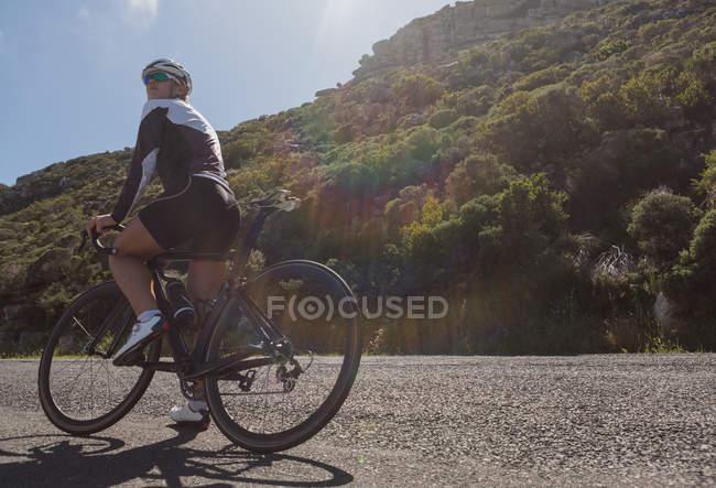 Велосипедистка отдыхает на дороге в солнечный день — стоковое фото