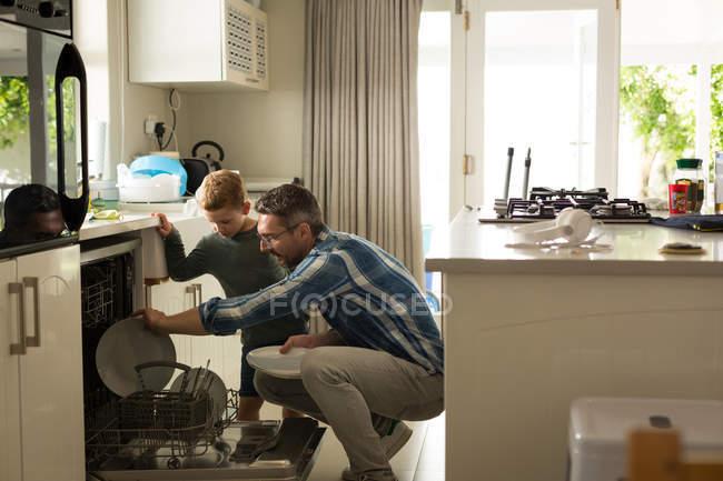 Père et fils arrangeant des ustensiles dans la cuisine à la maison — Photo de stock