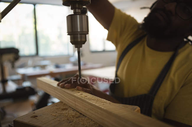 Nahaufnahme des Tischlers beim Bohren von Holzplanken mit Maschine in der Werkstatt — Stockfoto