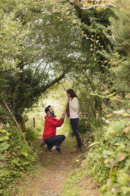 Affettuoso uomo posa ragazza sotto albero baldacchino in campagna — Foto stock