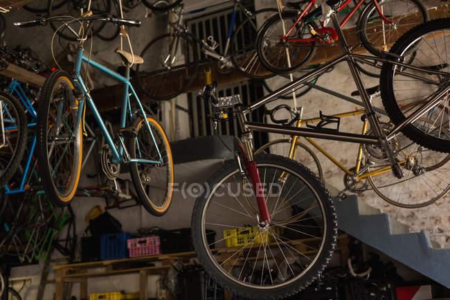 Різних велосипедів висить в майстерні — стокове фото