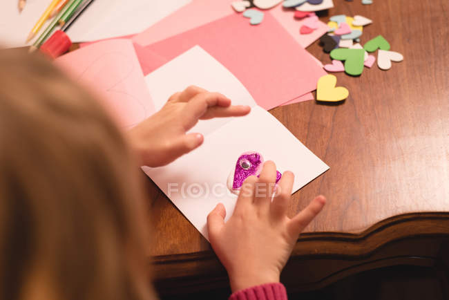 Girl preparing heart shape decoration at home — Stock Photo