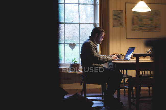 Attentive man using laptop at home — Stock Photo