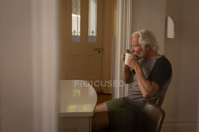 Active senior man having coffee at home — Stock Photo