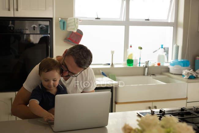Father and son using laptop in kitchen at home — Stock Photo
