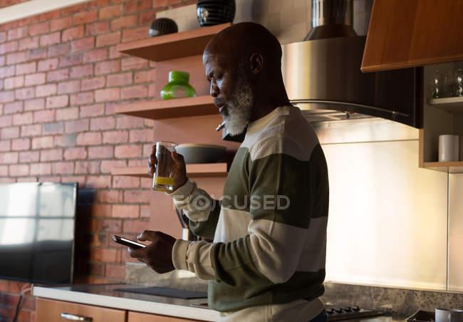 Senior man having juice while using mobile phone at home — Stock Photo