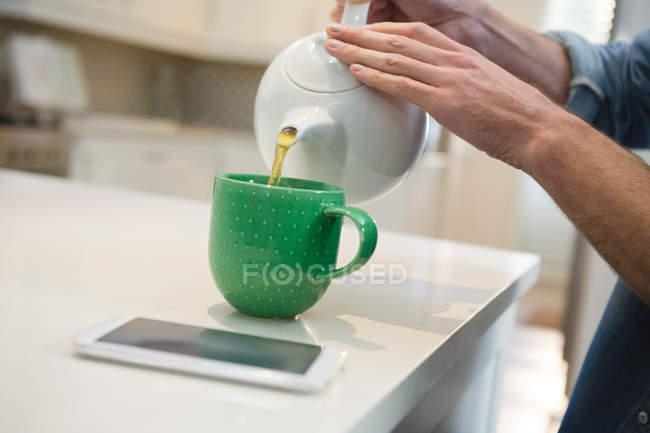 Mid section of man pouring lemon tea into mug at home — Stock Photo