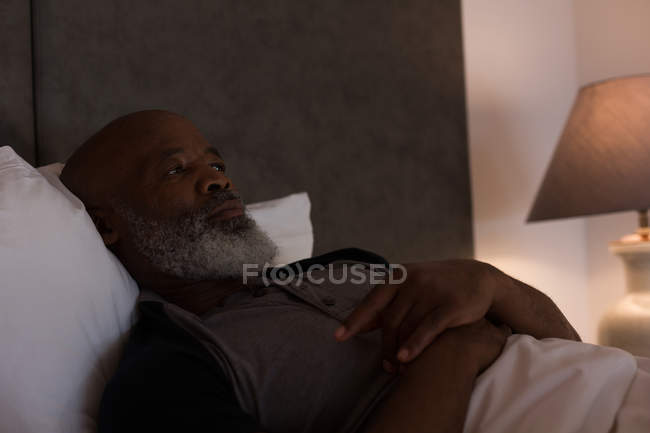 Senior man lying in bedroom at home — Stock Photo