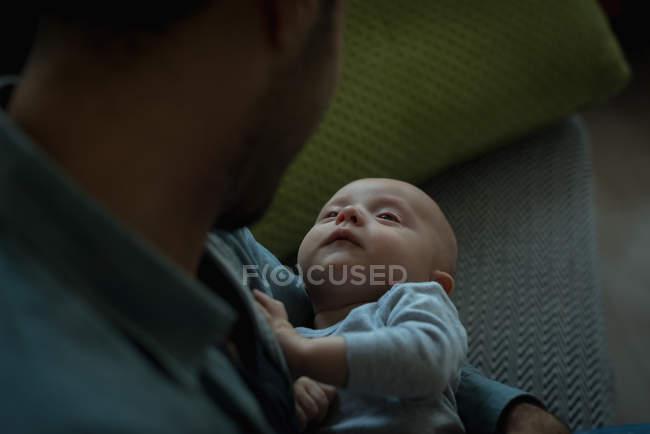 Padre sosteniendo a su bebé en la sala de estar en casa - foto de stock