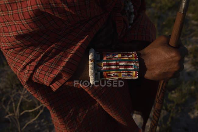 Mittleren Bereich der Maasai Mann in traditioneller Kleidung stehend mit Stab — Stockfoto