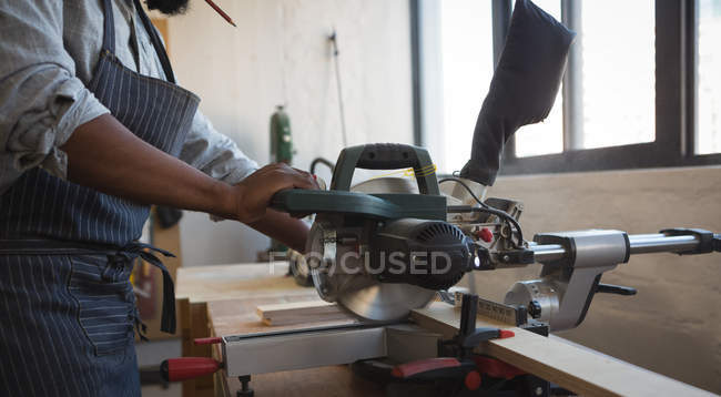Mid section of carpenter cutting wooden plank with electric saw in workshop — Stock Photo
